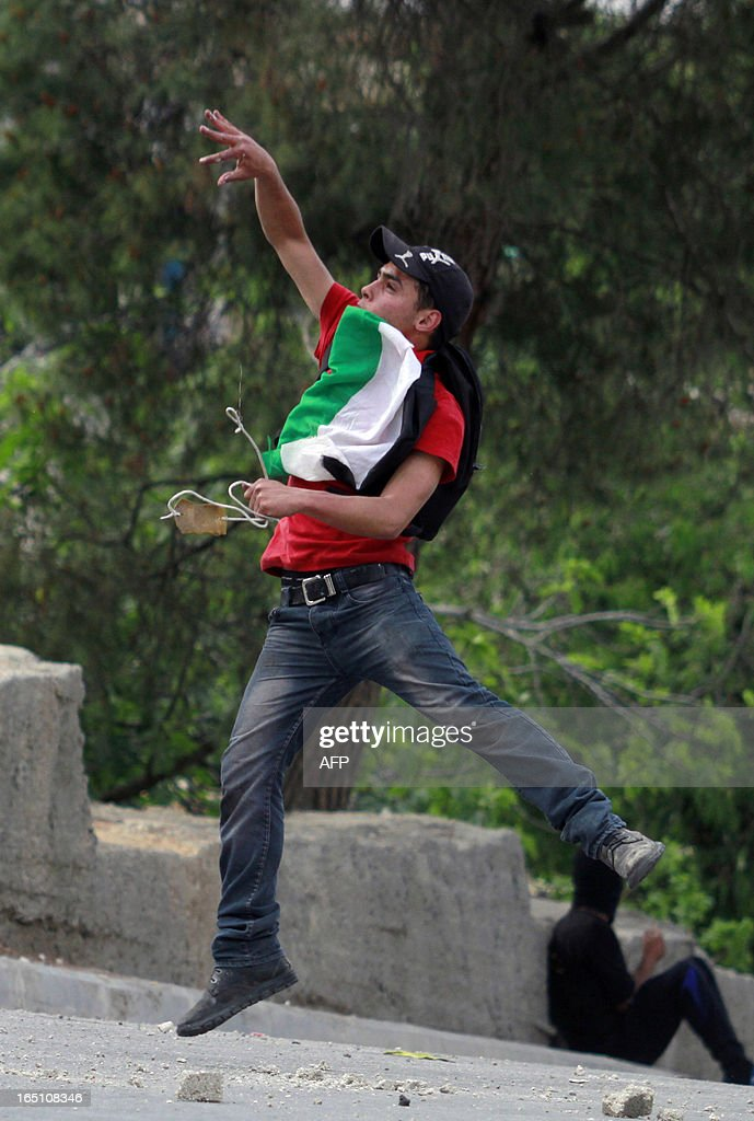 A Palestinian protester throws stones towards Israeli soldiers during clashes following a rally marking Land Day in the al-khader village near the West Bank town of Bethlehem on March 30, 2013. The annual demonstrations mark the deaths of six Arab Israeli protesters at the hands of Israeli police and troops during mass protests in 1976 against plans to confiscate Arab land in the northern Galilee region.