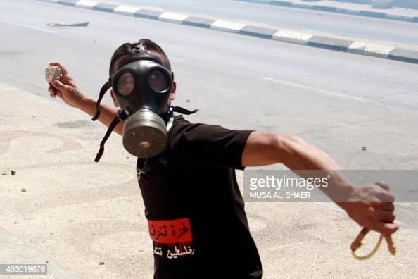 A Palestinian protester throws stones towards Israeli troops during clashes on August 1 2014 near the main entrance of the West bank city of...