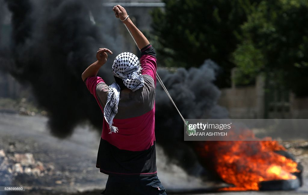 A Palestinian protester throws stones using a sling shot towards Israeli security forces during clashes following a weekly demonstration against the expropriation of Palestinian land by Israel in the village of Kfar Qaddum, near Nablus, in the occupied West Bank, on May 6, 2016. / AFP / JAAFAR