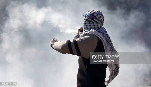 A Palestinian protester throws teargas canister back at Israeli forces during clashes following a weekly demonstration against the expropriation of...