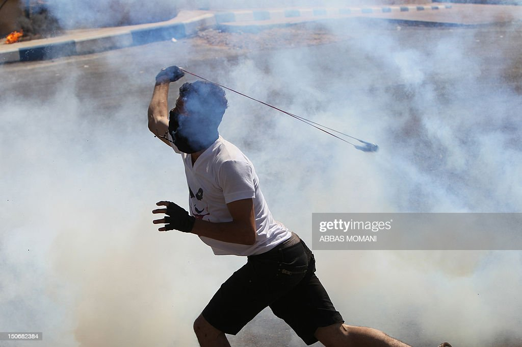 A Palestinian protester uses a sling shot to stone Israeli soldiers during clashes following a demonstration in the West Bank village of Nabi Saleh in protest against the confiscation of Palestinian land to expand the nearby Jewish settlement of Halamish on August 24, 2012. The weekly demonstrations in Nabi Saleh began at the end of 2009, following a years-long legal battle with residents of Halamish settlement who in 2001 seized around 240 acres (100 hectares) of the villagers' land.