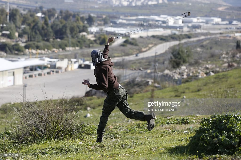 A Palestinian protester uses a sling shot to throw stones at Israeli forces during clashes that followed a demonstration on February 12, 2016 in solidarity with Palestinian prisoners held in Israeli jails, outside the compound of the Israeli-run Ofer Prison near Betunia in the occoupied West Bank. / AFP / ABBAS MOMANI