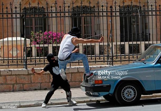 A Palestinian protester uses a sling shot to throw stones towards Israeli security forces during clashes following a demonstration marking the 69th...