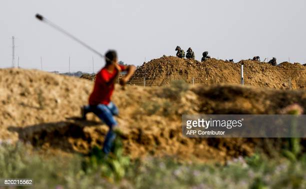 Palestinian protester uses a sling to hurl a stone towards Israeli troops during clashes with Israeli security forces near the border fence east of...