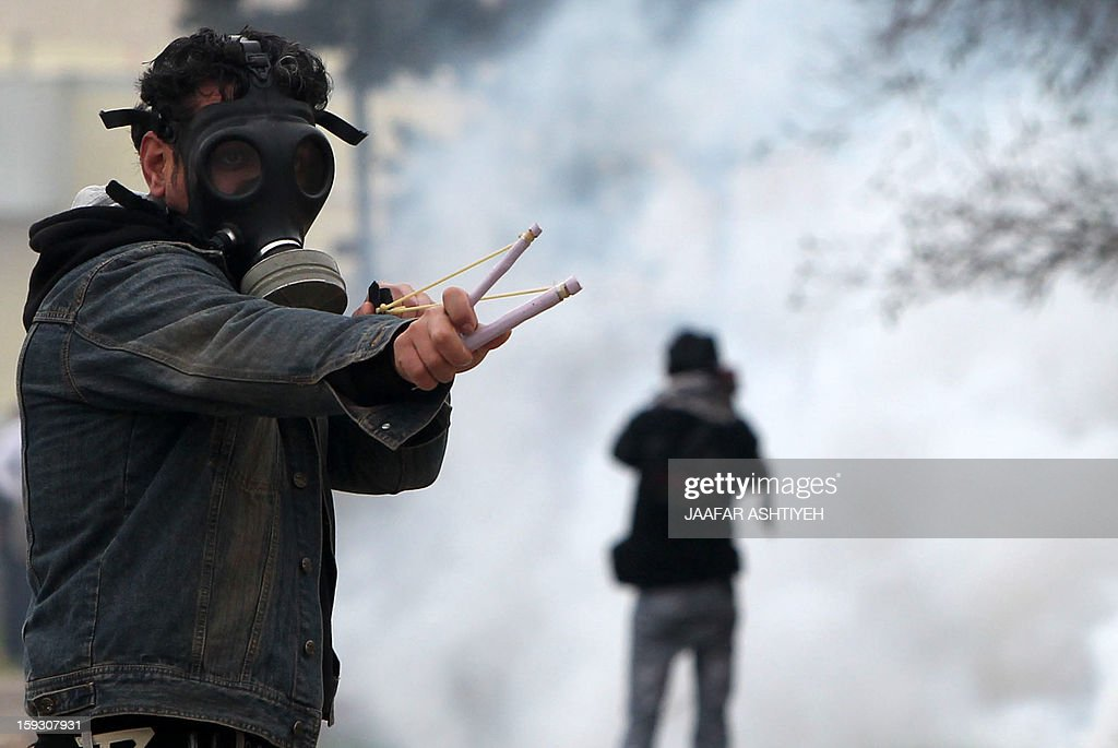 A Palestinian protester uses a slingshot during a protest against the expropriation of Palestinian land by Israel on January 11, 2013 in the village of Kafr Qaddum, near Nablus, in the occupied West Bank. AFP PHOTO/JAAFAR ASHTIYEH