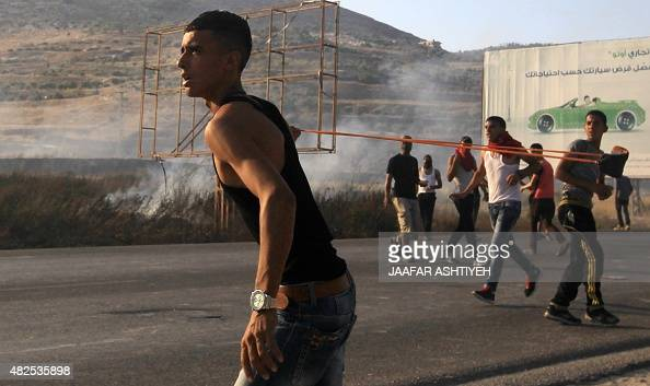 A Palestinian protester uses a slingshot during clashes with Israeli security forces on July 31 2015 at the Israelimaned Hawara checkpoint south of...