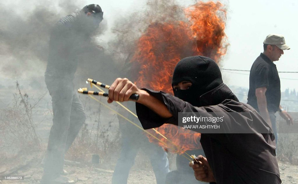 A Palestinian protester uses a slingshot to hurl a stone at Israeli soldiers during a demonstration against the expropriation of Palestinian land by Israel in the village of Kafr Qaddum in the occupied West Bank on June 15, 2012. Envoys from the Middle East Quartet met in Brussels amid calls from the Palestinians to step up action to halt continuing Israeli settlement activity in the occupied territories.
