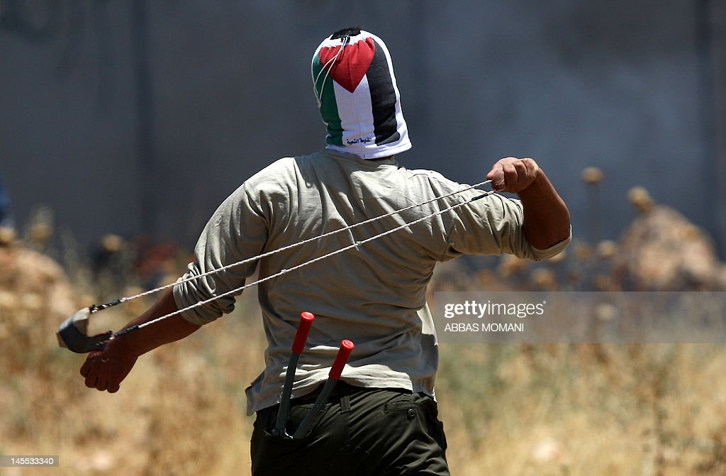 A Palestinian protester uses a slingshot to hurl a stone towards Israeli troops during a weekly demonstration against Israel's controversial separation barrier in the West Bank village of Nilin on June 1, 2012. When completed, 85 percent of the wall will have been built inside the West Bank, taking land from Palestinian villages like Bilin and Nilin.