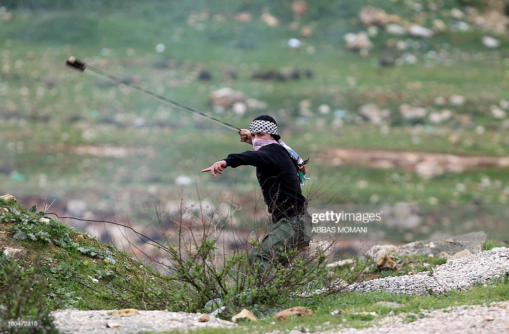 A Palestinian protester uses a slingshot to hurl stones towards Israeli troops during clashes following a demonstration organised by residents of the West Bank village Nabi Saleh to protest against the expansion of Jewish settlements on Palestinian land on February 1, 2013.