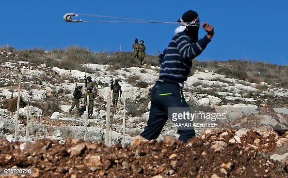 Palestinian protester uses a slingshot to hurl stones towards Israeli security forces during clashes following a demonstration against the...
