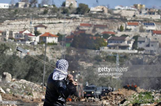 A Palestinian protester uses a slingshot to hurl stones towards Israeli security forces during clashes following a weekly demonstration against the...