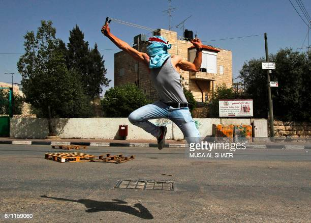 Palestinian protester uses a slingshot to hurl stones towards Israeli security forces during clashes following a demonstration in the West Bank town...