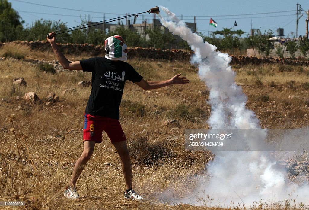 A Palestinian protester uses a slingshot to throw back a tear gas canister at Israeli soldiers during clashes in the West Bank village of Nabi Saleh, near Ramallah, on June 8, 2012, during a protest against the confiscation of Palestinian land to expand Jewish settlements. MOMANI