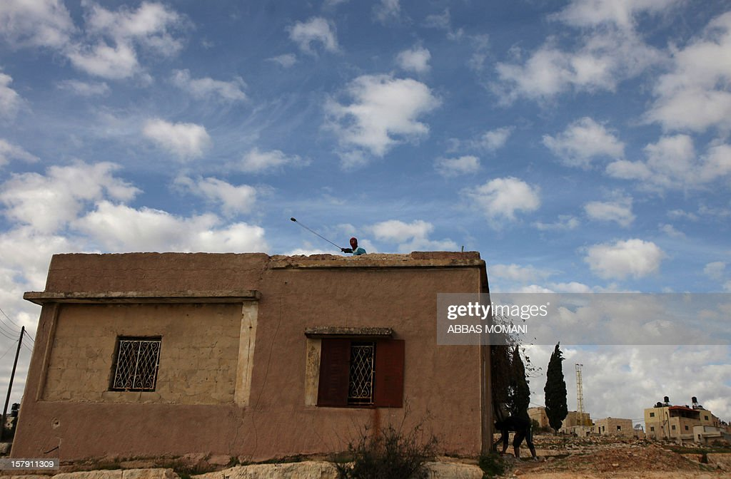 A Palestinian protester uses a slingshot to throw stones from the roof of a house during clashes with Israeli soldiers following a demonstration against the expropriation of Palestinian land by Israel in the West Bank village of Nabi Saleh on December 7, 2012.
