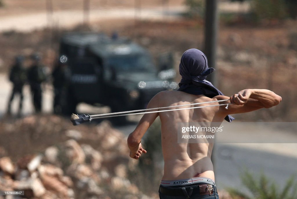 A Palestinian protester uses a slingshot to throw stones towards Israeli soldiers during a weekly demonstration against the confiscation of Palestinian land by Israel in the central West Bank village of Nabi Saleh near Ramallah on September 28, 2012.