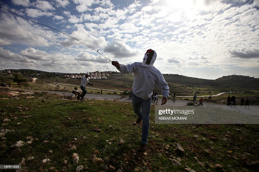 A Palestinian protester uses a slingshot to throw stones towards Israeli soldiers during clashes following a demonstration against the expropriation of Palestinian land by Israel in the West Bank village of Nabi Saleh on December 7, 2012.
