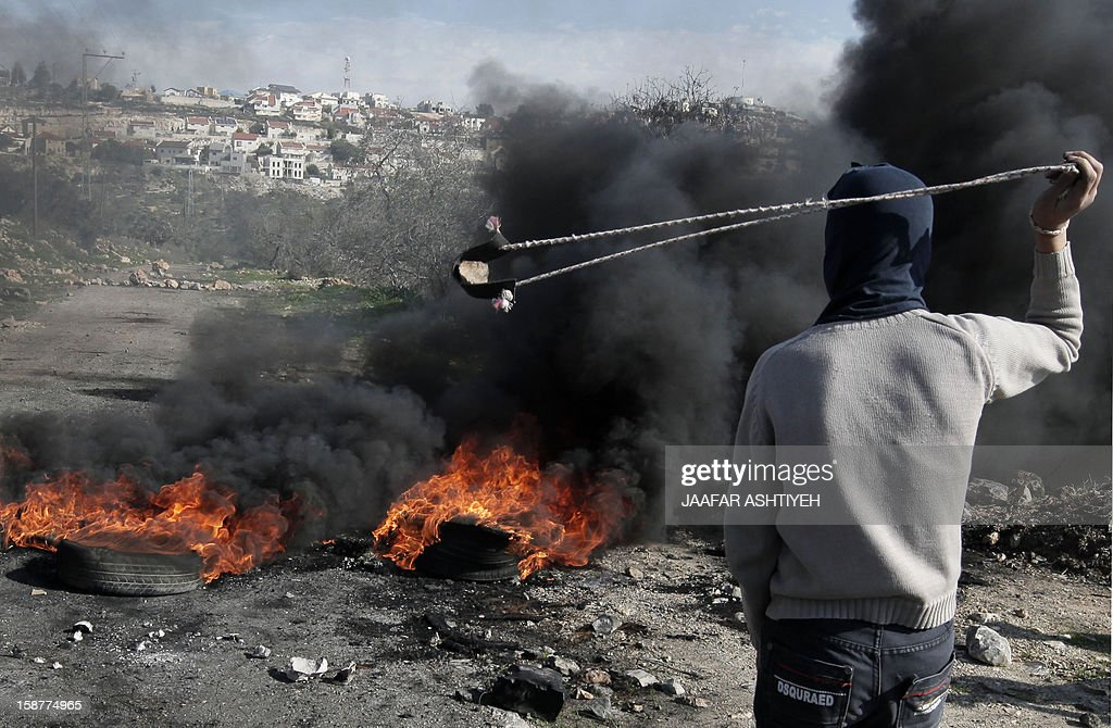 A Palestinian protester uses a slingshot to throw stones towards Israeli soldiers (unseen) during clashes following a demonstration against the expropriation of Palestinian land by Israel in the village of Kfar Qaddum, near the occupied West Bank city of Nablus, on December 28, 2012. AFP PHOTO / JAAFAR ASHTIYEH