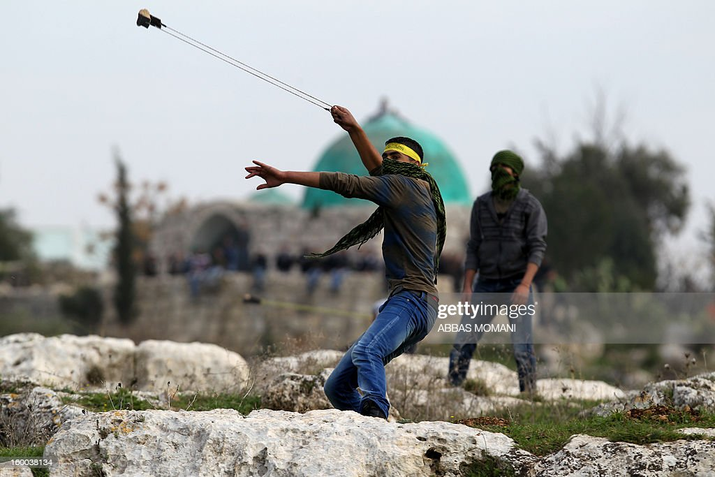 A Palestinian protester uses a slingshot to throw stones towards Israeli soldiers during a demonstration against the expansion of Jewish settlements on Palestinian land in the village of Budrus, west of the West Bank city of Ramallah, on January 25, 2013.