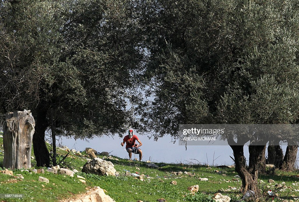A Palestinian protester waits to throw stones towards Israeli security forces during clashes that erupted following a march organised by residents of the West Bank village Nabi Saleh to protest against the expansion of Jewish settlements on Palestinian land on December 28, 2012.
