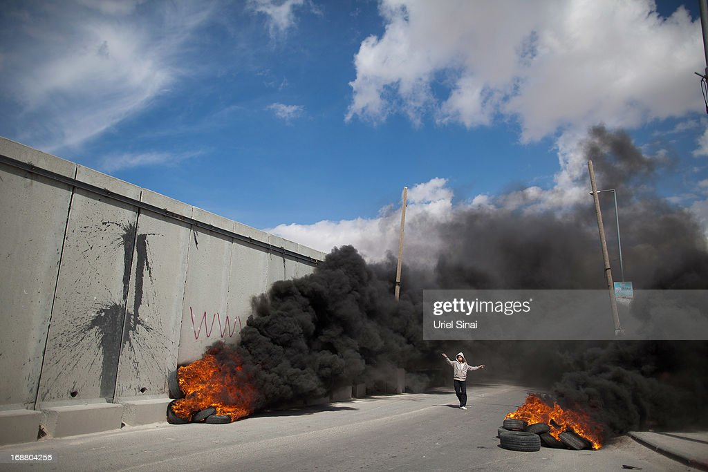A Palestinian protester walks between burning tires during clashes with the Israeli army during Nakba day on May 15, 2013 near the Qalandia checkpoint at the outskirts of Ramallah, the West Bank. Palestinians mark Israel's establishment in 1948 with 'Nakba' or 'catastrophe' day on May 15, to remember the thousands of Palestinians who fled or were expelled during the creation of the Jewish state and the subsequent war.