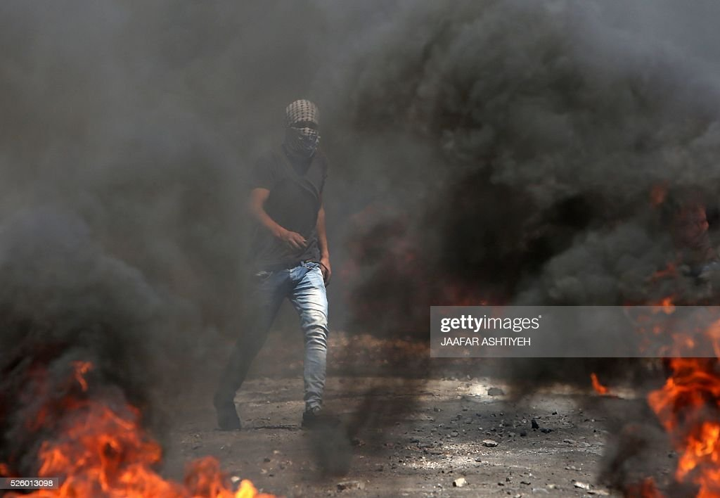 A Palestinian protester walks past burning tires during clashes with Israeli security forces following a demonstration against the expropriation of Palestinian land by Israel on April 29, 2016 in the village of Kfar Qaddum, near Nablus, in the occupied West Bank. / AFP / JAAFAR