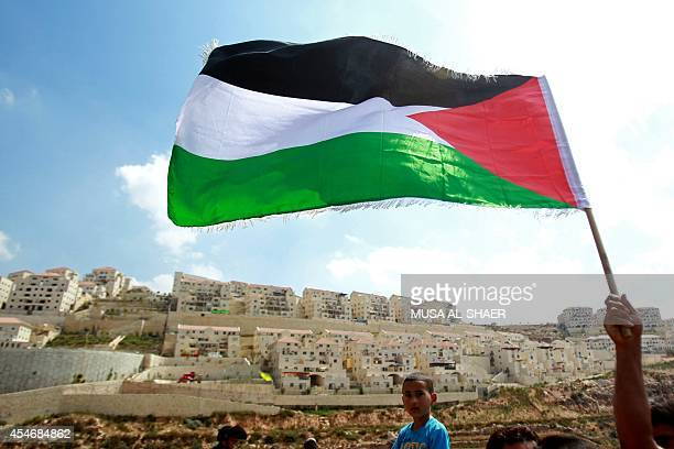 A Palestinian protester waves a national flag in front of the Israeli settlement of Beitar Illit near the West Bank village of Wadi Fukin on...