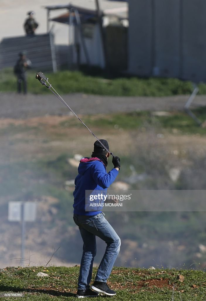 A Palestinian protester waves a sling shot towards Israeli troops during clashes following a protest on February 12, 2016 in solidarity with Palestinian prisoners held in Israeli jails, outside the compound of the Israeli-run Ofer Prison near Betunia in the occoupied West Bank. / AFP / ABBAS MOMANI