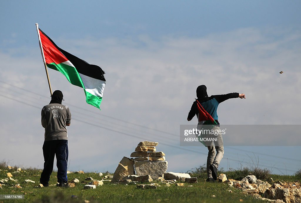 A Palestinian protester waves his national flag next to a fellow demonstrator throwing stones towards Israeli security forces during clashes that erupted following a march organised by residents of the West Bank village Nabi Saleh to protest against the expansion of Jewish settlements on Palestinian land on December 28, 2012.