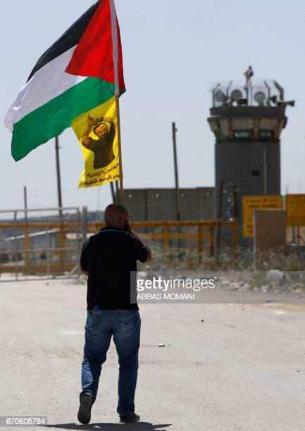 A Palestinian protester waves the national flag and a portrait of prominent prisoner and popular leader Marwan Barghouti during a demonstration in...