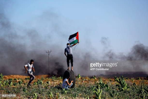 Palestinian protester waves the national flag during clashes with Israeli security forces near the border fence east of Jabalia refugee camp on June...