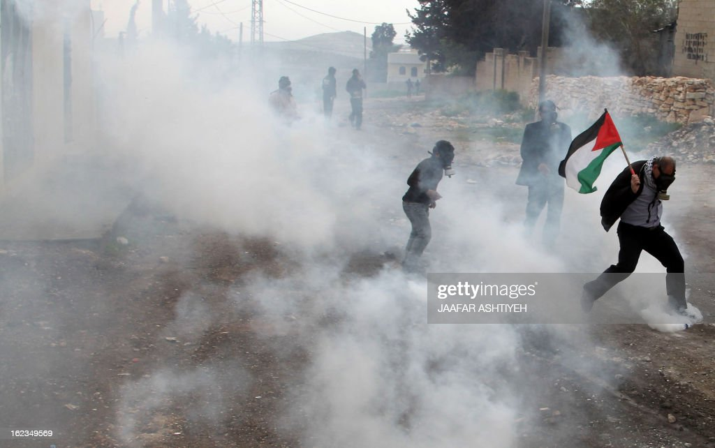 A Palestinian protester waving his national flag runs for cover from tear gas fired by Israeli troops during clashes following a demonstration in support of Palestinian hunger-striking prisoners and against the expropriation of Palestinian land by Israel in the village of Kfar Qaddum near Nablus in the occupied West Bank on February 22, 2013. Palestinians demanding the release of hunger-striking prisoners clashed with Israelis in the West Bank and east Jerusalem, as three fasting inmates were taken to hospitals. AFP PHOTO/JAAFAR ASHTIYEH