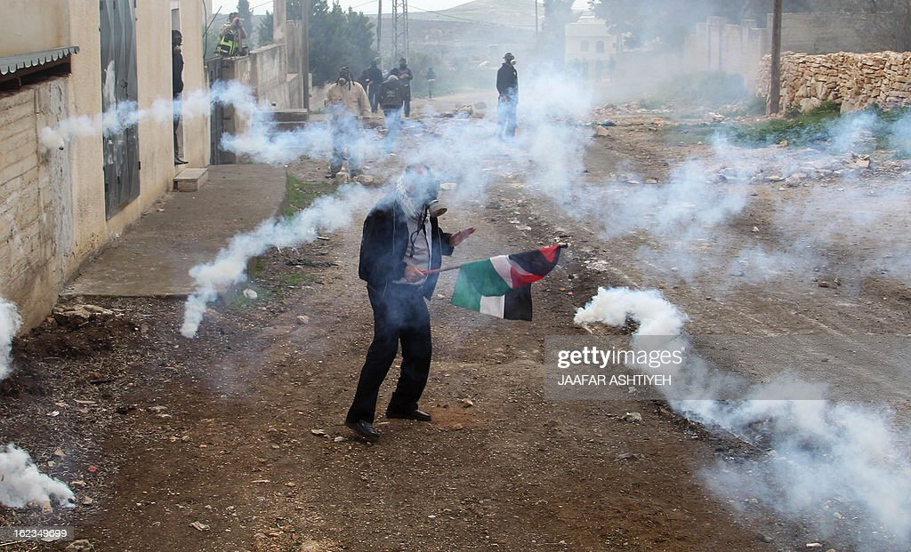 A Palestinian protester wearing a gas mask holds his national flag as he stands amid a fog of tear gas fired by Israeli troops during clashes following a demonstration in support of Palestinian hunger-striking prisoners and against the expropriation of Palestinian land by Israel in the village of Kfar Qaddum near Nablus in the occupied West Bank on February 22, 2013. Palestinians demanding the release of hunger-striking prisoners clashed with Israelis in the West Bank and east Jerusalem, as three fasting inmates were taken to hospitals. AFP PHOTO/JAAFAR ASHTIYEH
