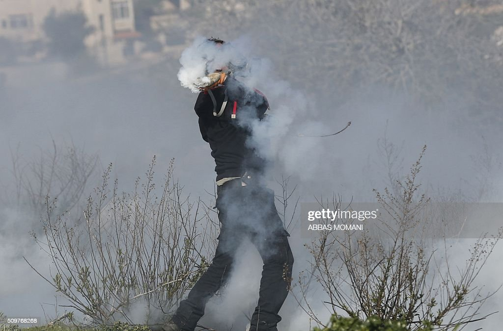 A Palestinian protester wearing a masque against tear gas is covered with smoke during clashes with Israeli forces following a protest on February 12, 2016 in solidarity with Palestinian prisoners held in Israeli jails, outside the compound of the Israeli-run Ofer Prison near Betunia in the occoupied West Bank. / AFP / ABBAS MOMANI