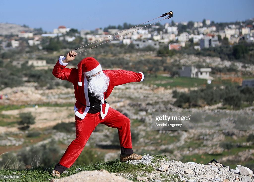 A Palestinian protester wearing a Santa Claus costume throws stones at Israeli soldiers during a protest against the construction of Jewish settlement housing and the separation wall in Ramallah, West Bank on December 25, 2015.