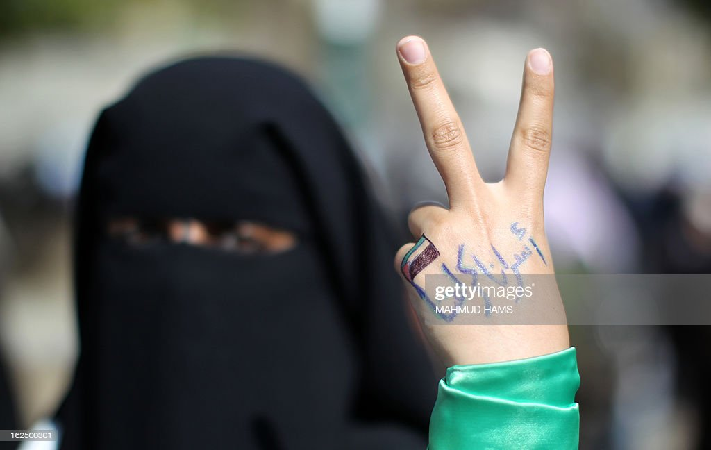 A Palestinian protester whose hand reads in Arabic 'Our prisoners are our dignity' makes the victory sign during a demonstration in Gaza City in solidarity with Palestinian prisoners on February 24, 2013. Some 3,000 Palestinians held in Israeli jails were staging a one-day hunger strike in protest at the death of an inmate, an official said, as security forces clashed with demonstrators in the West Bank. AFP PHOTO / MAHMUD HAMS