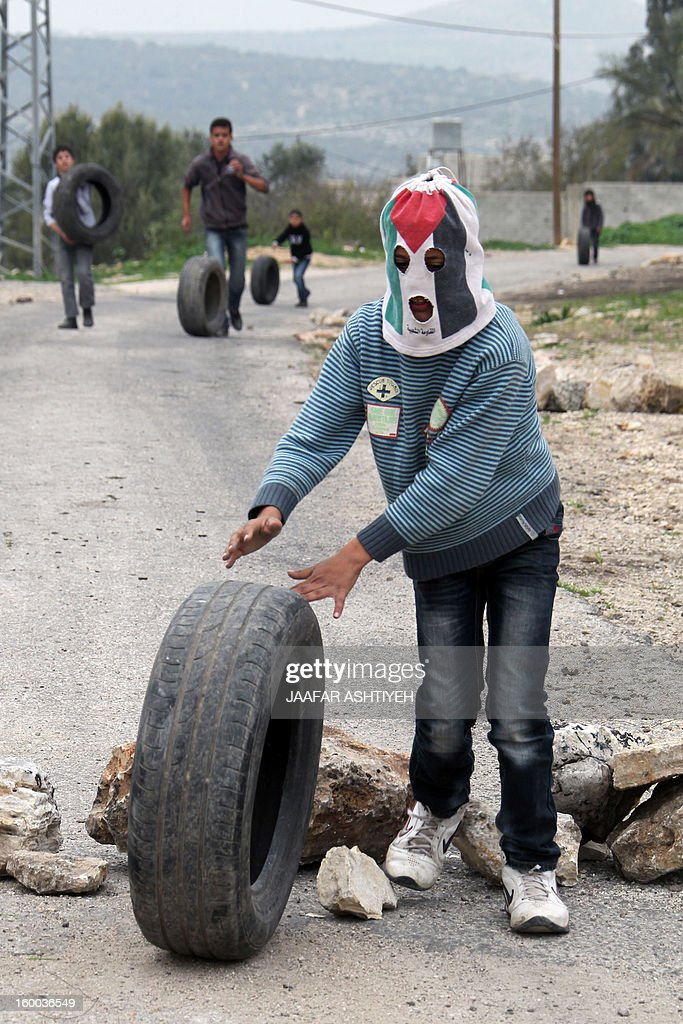 A Palestinian protester, whose head is covered, rolls a tyre during a protest against the expropriation of Palestinian land by Israel on January 25, 2013 in the village of Kafr Qadum, near Nablus, in the occupied West Bank. AFP PHOTO/JAAFAR ASHTIYEH
