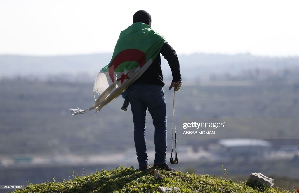 A Palestinian protester with an Algerian flag covering his back holds a sling shot during clashes with Israeli forces following a demonstration on February 12, 2016 in solidarity with Palestinian prisoners held in Israeli jails, outside the compound of the Israeli-run Ofer Prison near Betunia in the occoupied West Bank. / AFP / ABBAS MOMANI