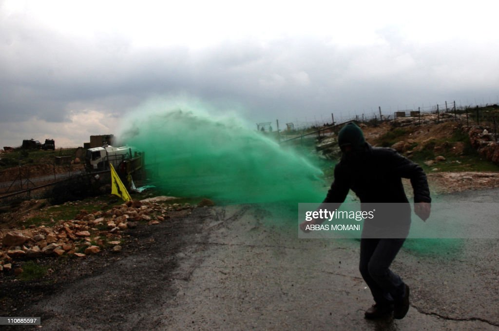 A Palestinian protester with stones in his hands runs a way as colored water is sprayed by the Israeli army from a water canon during the weekly demonstration against Israel's controversial separation barrier in the village of Bilin, near the West Bank city of Ramallah on March 11, 2011.