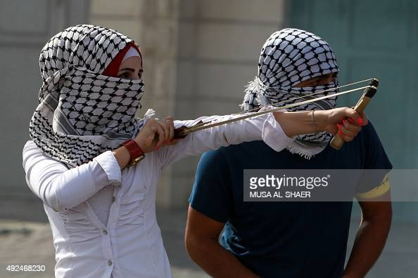 A Palestinian protester young woman uses a slingshot to throw stones during clashes with Israeli security forces on October 13 2015 in the West Bank...