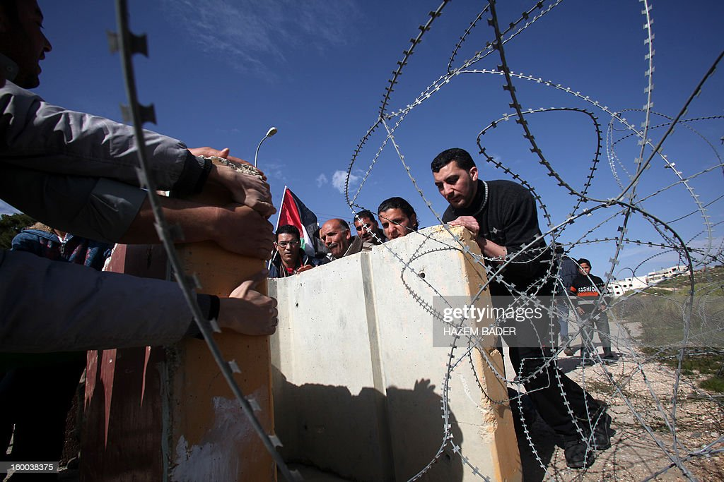 Palestinian protesters along with Israeli and foreign peace activists try to remove barricades to open one of the main entrances to the West Bank city of Hebron which is closed by Israeli troops due to its proximity to the Jewish settlement of Beit Hagay on January 25, 2013. AFP PHOTO / HAZEM BADER