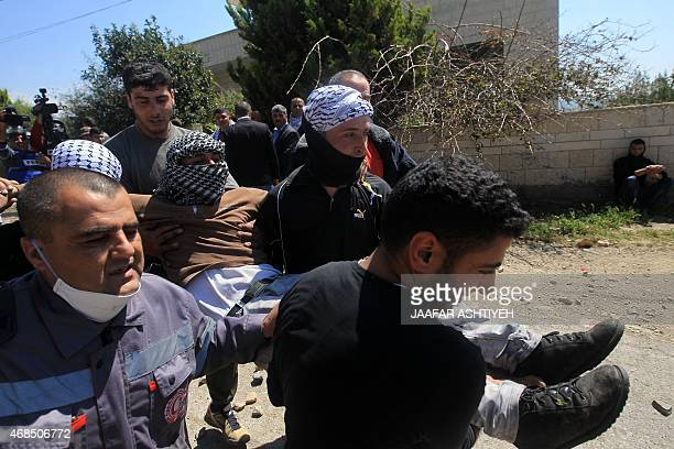 Palestinian protesters and a Red Crescent medic carry an injured man during clashes with Israeli security forces following a demonstration against...