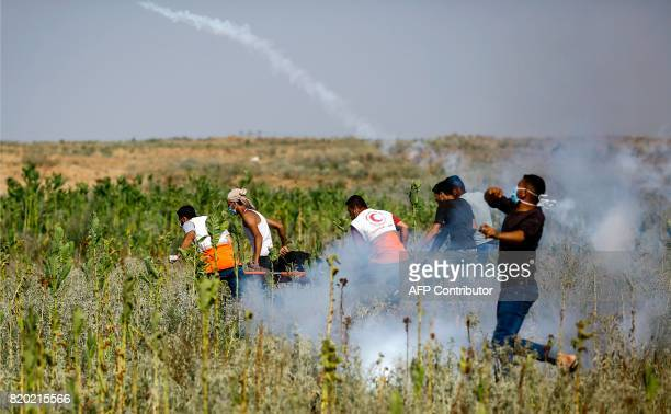 Palestinian protesters and medics carry a wounded man while another throws back a teargas canister fired by Israeli troops during clashes with...