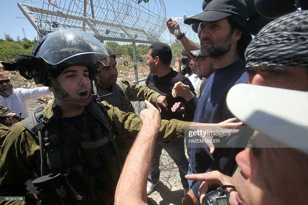 Palestinian protesters are stopped by Israeli soldiers at the entrance of the Karmi Tsour settlement during a protest against settlement expansion on Palestinian land in the Beit Omar village, north the West Bank city of Hebron, on April 26, 2013. Israeli security forces overnight demolished two structures that Jewish settlers had erected to create a 'wildcat' outpost in the occupied West Bank, a police spokesman said on April 26. AFP PHOTO/HAZEM BADER