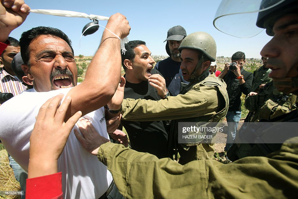 Palestinian protesters are stopped by Israeli soldiers during a protest against settlement expansion on Palestinian land in the Beit Omar village, north the West Bank city of Hebron, on April 26, 2013. Israeli security forces overnight demolished two structures that Jewish settlers had erected to create a 'wildcat' outpost in the occupied West Bank, a police spokesman said on April 26.