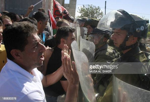 Palestinian protesters argue with Israeli soldiers as they take part in a weekly demonstration against the Israeli separation barrier and the...