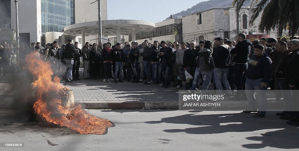 Palestinian protesters burn tires and block the streets in the northern West Bank city of Nablus as they protest against the economic situation and against Palestinian prime minister Salam Fayyad on December 31, 2012. The protest came after Fayyad announced that the Palestinian Authority would as of 2013 enforce the payment of electricity bills by refugee camp residents, who have so far not had to pay them. AFP PHOTO /JAAFAR ASHTIYEH