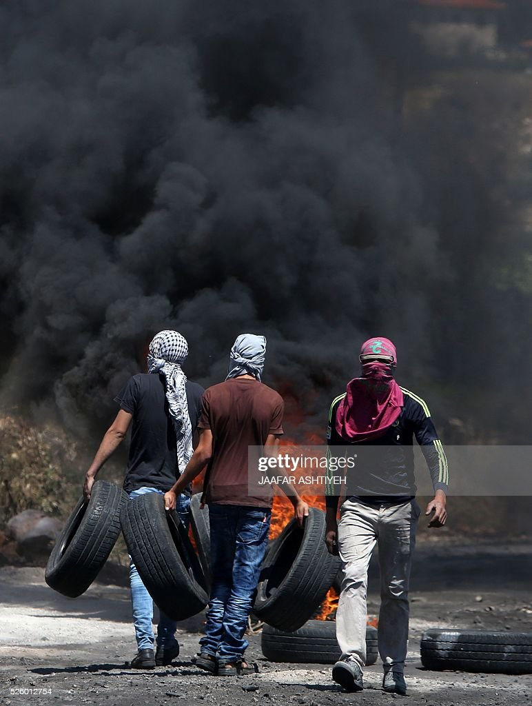 Palestinian protesters burn tires during clashes with Israeli security forces following a demonstration against the expropriation of Palestinian land by Israel on April 29, 2016 in the village of Kfar Qaddum, near Nablus, in the occupied West Bank. / AFP / JAAFAR