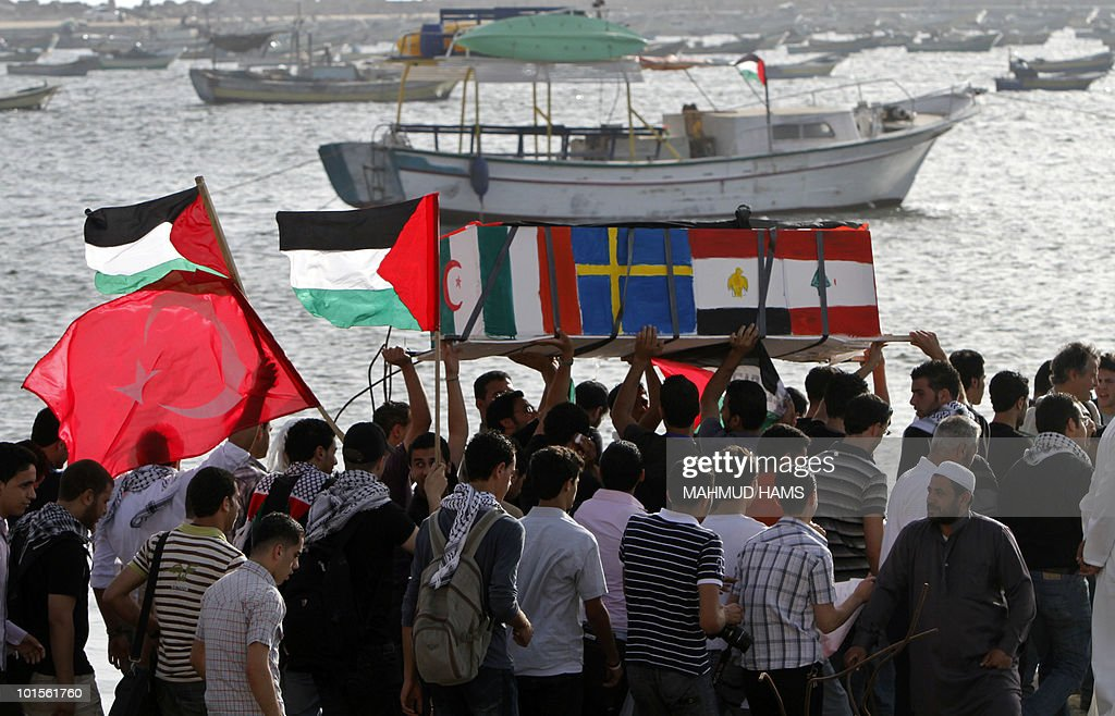 Palestinian protesters carry a mock coffin during a demonstration in the port of Gaza City on June 2, 2010 against Israel's deadly raid on a Gaza-bound aid flotilla on May 31.
