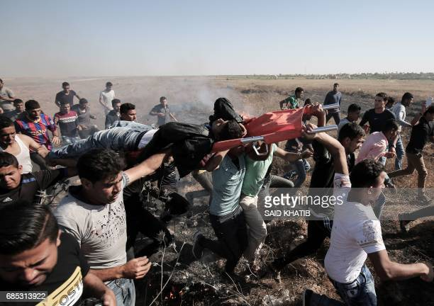 TOPSHOT Palestinian protesters carry a wounded comrade during clashes with Israeli soldiers following a protest against the blockade on Gaza near the...