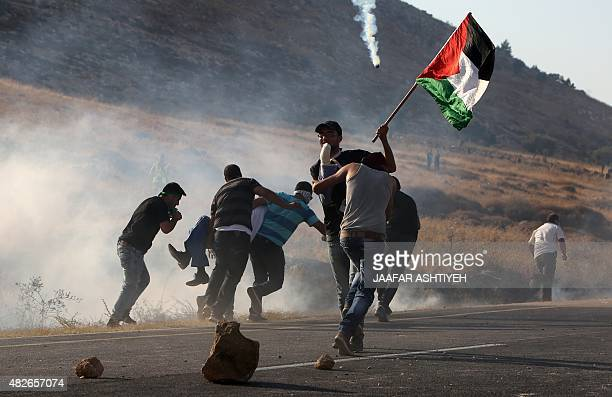 Palestinian protesters carry an injured comrade during clashes with Israeli security forces on a street leading to Duma village on August 1 following...